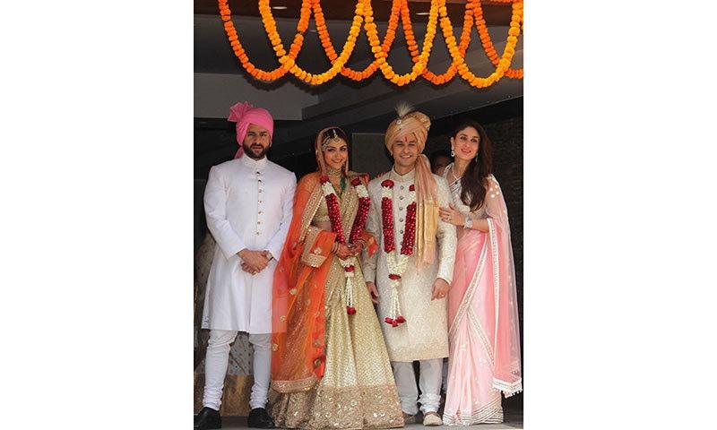 Indian Bollywood actor Saif Ali Khan (L) with his wife Kareena Kapoor Khan (R) attend the wedding of Soha Ali Khan (2nd L) and Kunal Khemu (2nd R) in Mumbai on January 25, 2015. — AFP