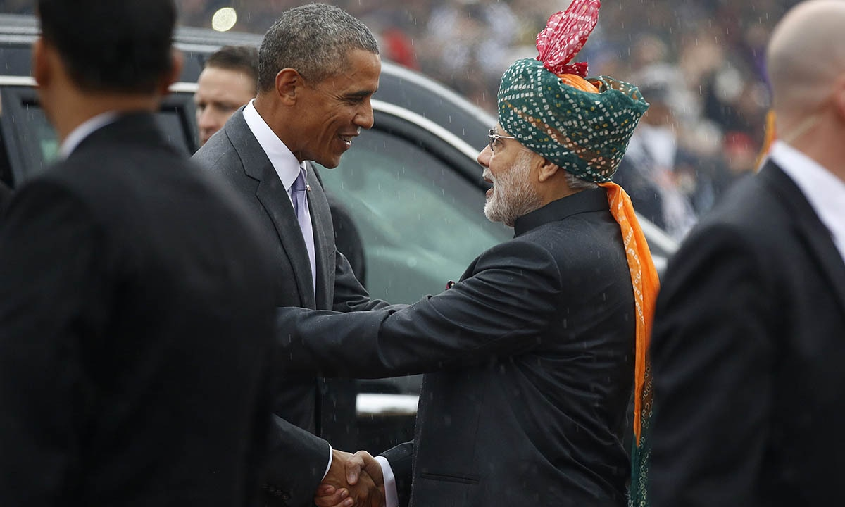 US President Barack Obama (L) shakes hands with India's Prime Minister Narendra Modi in the pouring rain as he arrives to attend the Republic Day parade in New Delhi January 26, 2015.  — Reuters