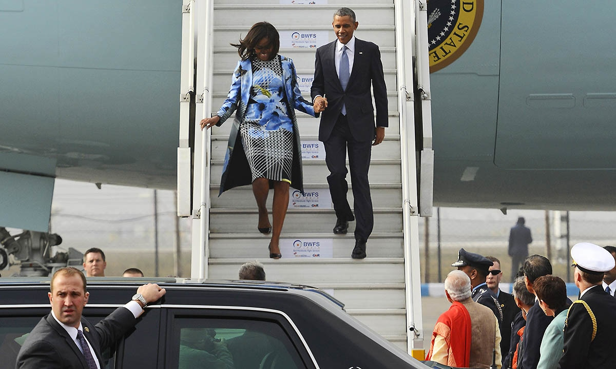 Indian Prime Minister Narendra Modi, bottom right wearing orange scarf, waits to welcome U.S. President Barack Obama and first lady Michelle Obama as they walk down an airstair upon arrival at the Palam Air Force Station in New Delhi, India, Sunday, Jan. 25, 2015. — AP