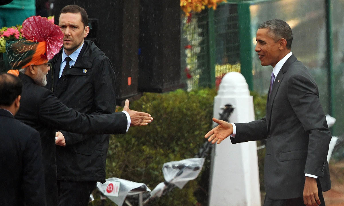 Indian Prime Minister Narendra Modi (L) welcomes US President Barack Obama (R) on Rajpath during India's Republic Day parade in New Delhi on January 26, 2015. Rain failed to dampen spirits at India's Republic Day parade January 26 as Barack Obama became the first US president to attend the spectacular military and cultural display in a mark of the nations' growing closeness. — AFP