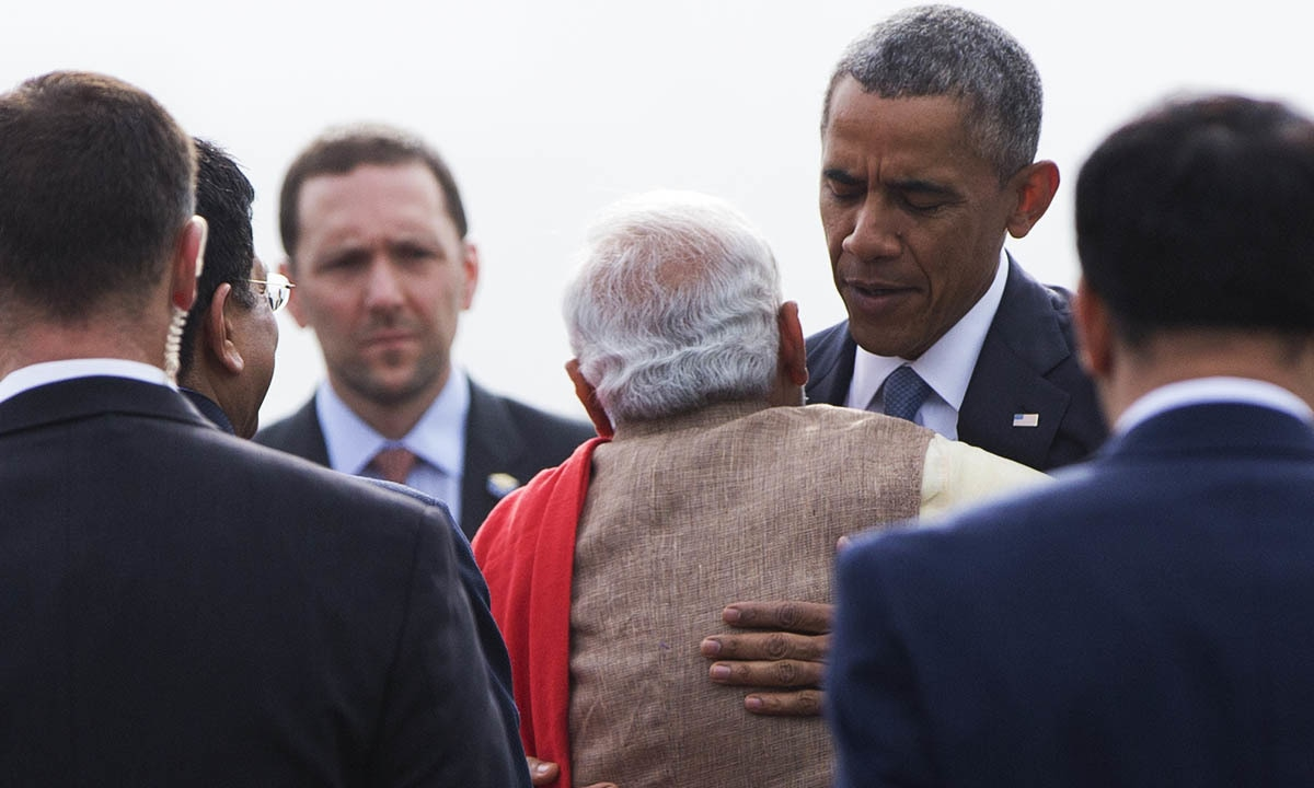 President Barack Obama embraces Indian Prime Minister Narendra Modi as he arrives with first lady Michelle Obama on Air Force One at Air Force Station Palam, in Palam, India, Sunday, Jan. 25, 2015. — AP