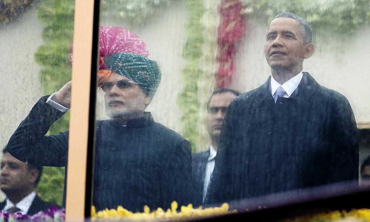 Indian Prime Minister Narendra Modi, left, and US President Barack Obama, right, look out through rain covered protective glass to watch the Republic Day Parade in New Delhi, India, Monday, Jan. 26, 2015. — AP