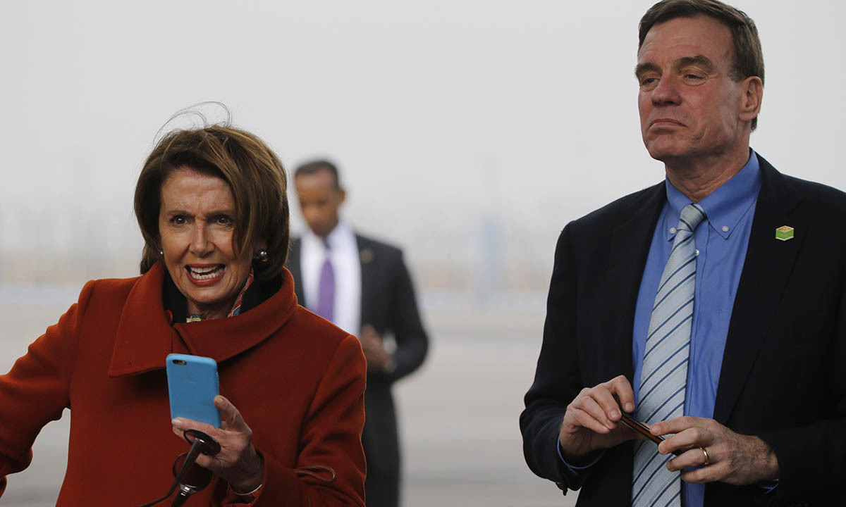 US House Minority Leader Nancy Pelosi (L) and US Senator Mark Warner wait to take pictures with phones of US President Barack Obama as he disembarks from Air Force One at Air Force Station Palam in New Delhi January 25, 2015.— Reuters