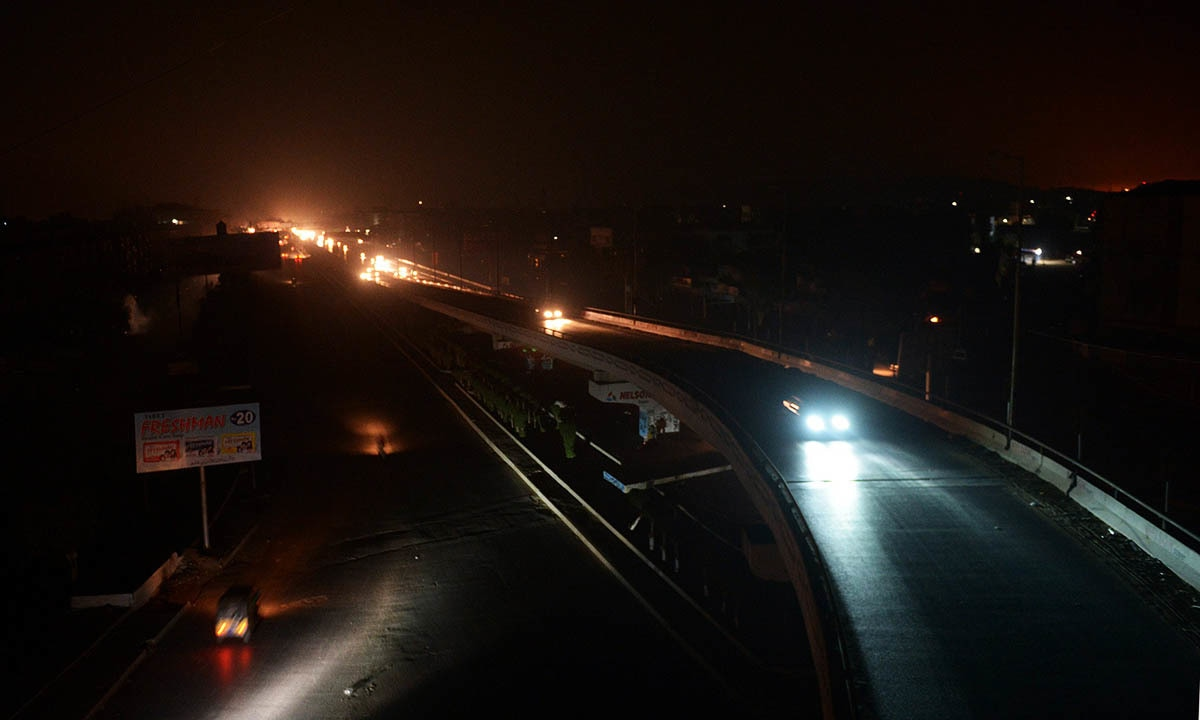 Motorists drive on an unlit street during a power cut in Karachi on January 25, 2015.— AFP