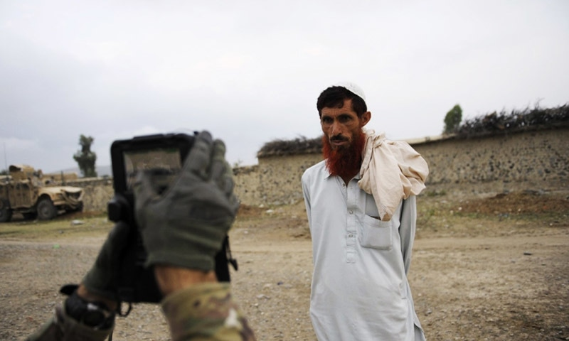 A US soldier collects biometric information from an Afghan villager. — AFP/file