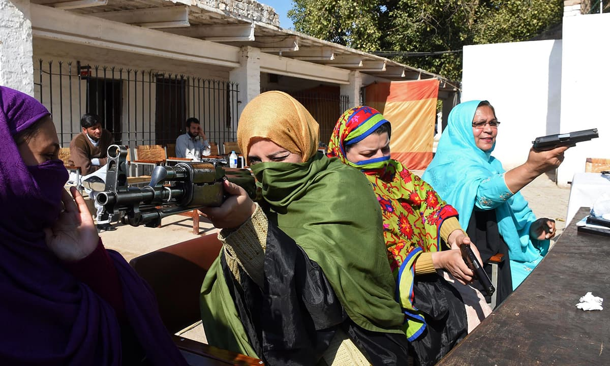 Teachers handle various firearms during a weapons training session for school, college and university teachers at a police training centre in Peshawar on January 27, 2015. — AFP