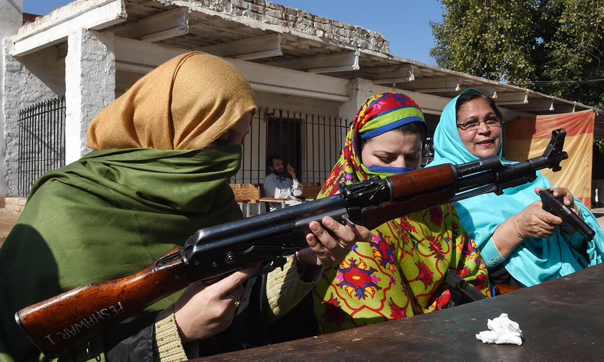 Pakistani teachers handle various firearms during a weapons training session for school, college and university teachers at a police training centre in Peshawar on January 27, 2015.  Authorities in northwest Pakistan have allowed teachers to carry firearms to schools and have begun weapons training for them, officials said. The decision was taken in the wake of a December 16, 2014 attack on an army-run school that killed 150 people, 134 of them children in Peshawar, the main town in the country's northwest. AFP PHO