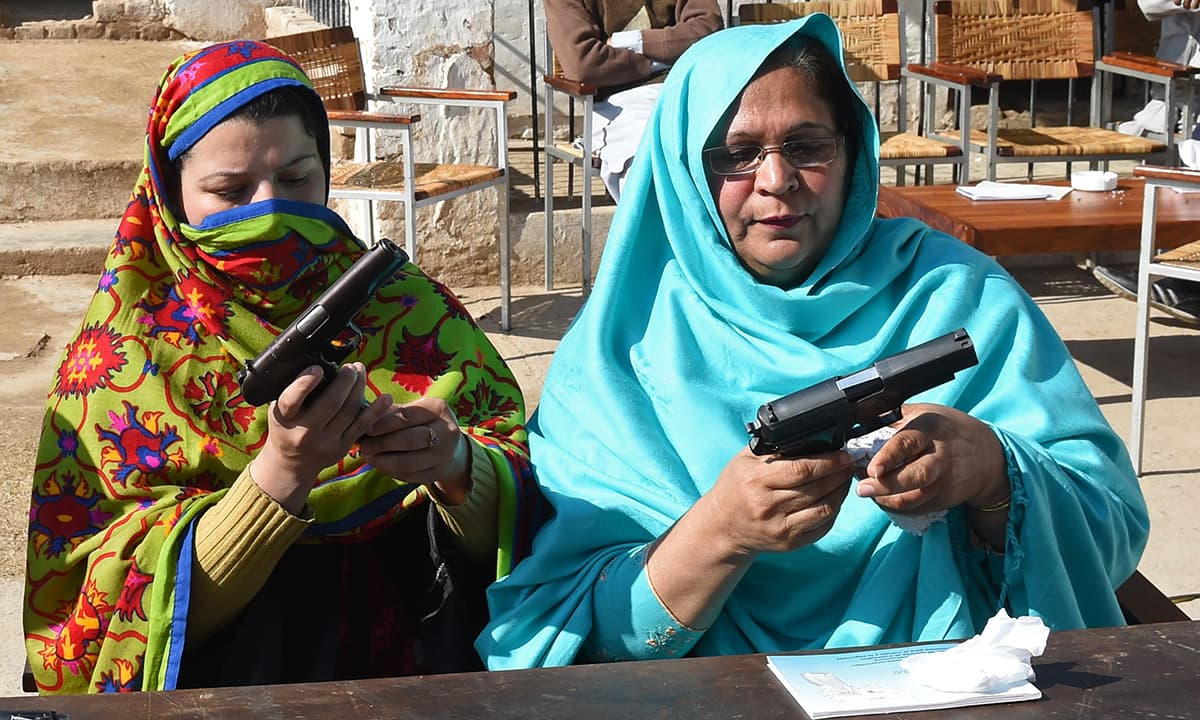 Teachers load magazines into pistols during a weapons training session for school, college and university teachers at a police training centre in Peshawar on January 27, 2015. — AFP