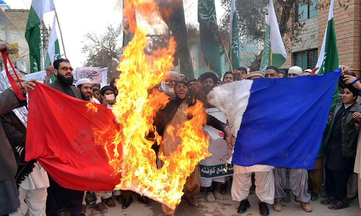 Protesters burn a French flag during a rally against the printing of sketches of the Prophet Muhammad (PBUH) by French magazine Charlie Hebdo in Quetta. — AFP