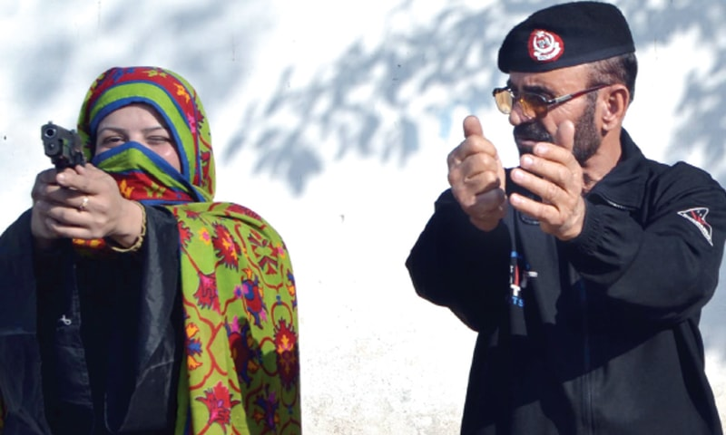 A policeman trains a teacher in firearms use at police lines, Peshawar, on Tuesday. — INP