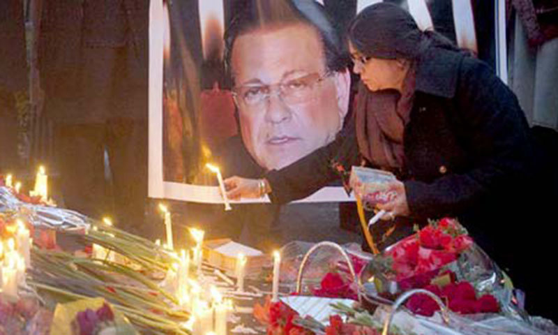 A woman lights a candle next to an image of the governor of Punjab Salman Taseer.—Reuters/File