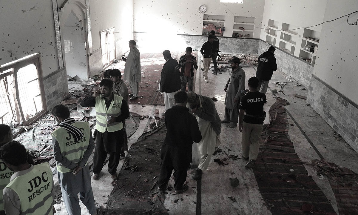 Security officials and police examine the scene following a bomb attack at an imambargah in Shikarpur. — AFP