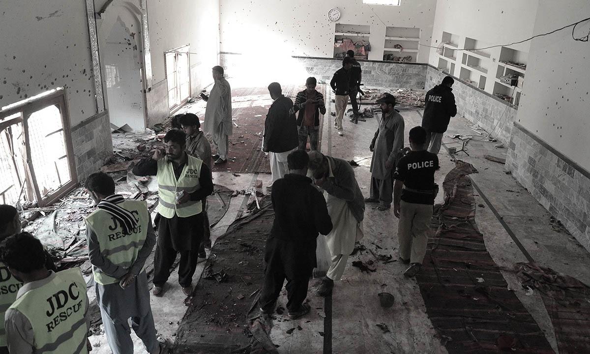 Сотрудники службы безопасности и полиция осмотреть место происшествия следующий взрыва бомбы на imambargah в Шикарпур.  - AFP