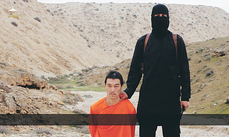 An IS militant standing next to Japanese journalist Kenji Goto before his beheading by the militant group on Jan 31.—AP