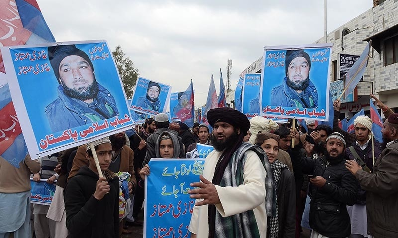 Supporters of Mumtaz Qadri, hold his portrait as they shout slogans calling for his release during a protest outside the high court building in Islamabad on February 3, 2015.— AFP