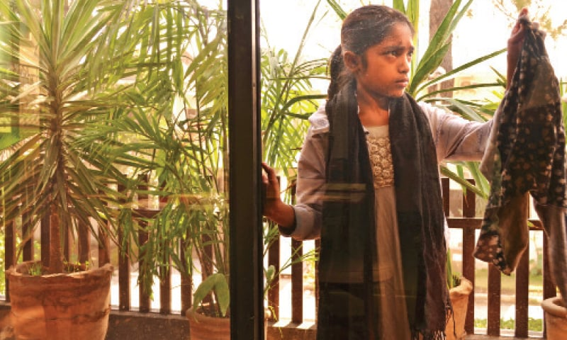 A girl cleans a window at a house where her mother works as a maid. — Photo by the writer