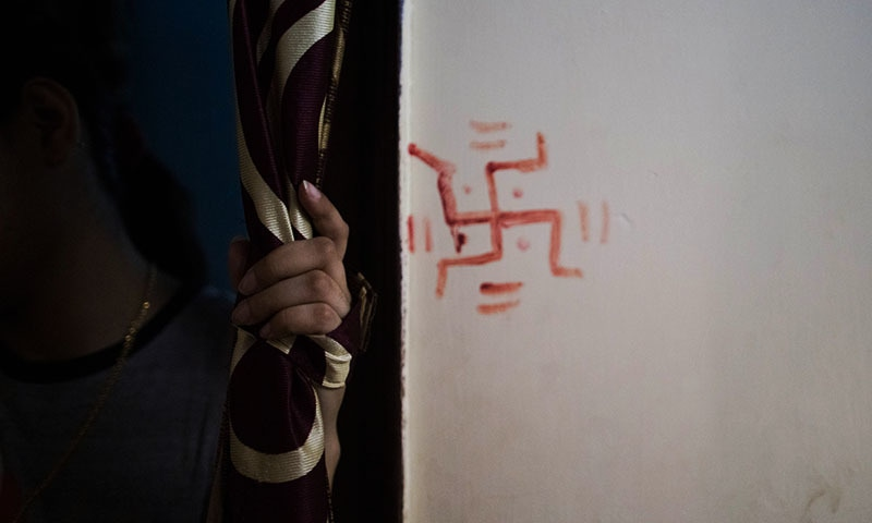 Indian resident Aisha, 24, who left her home to marry against her parents' wishes, stands in a doorway at one of seven shelters for couples who have left home to have 'love marriages' run by the Love Commandos NGO in New Delhi on September 21, 2014. — AFP