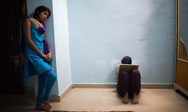 Indian residents Pinky (L), 21, and Aisha, 24, and who left their homes to marry against their parents' wishes, talk in their bedroom as Aisha uses a mirror to pluck her eyebrows at one of seven shelters for couples who have left home to have 'love marriages' run by the Love Commandos NGO in New Delhi on September 21, 2014.  — AFP