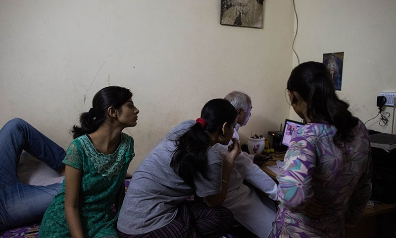 Indian residents Sara (L), 18,  Aisha (2L), 24, and Jyoti (R), 21, and who left their homes to marry against their parents' wishes, look at a newly-published article on a computer alongside the head of the Love Commandos NGO Sanjoy Sachdev at one of seven shelters for couples who have left home to have 'love marriages' run by the Love Commandos in New Delhi on September 21, 2014. — AFP