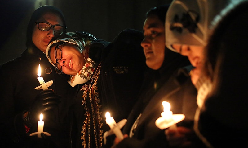 Nida Allam, a senior at North Carolina State University, rests her head on Asheen Allam, during a vigil for three people who were killed at a condominium near UNC-Chapel Hill, Wednesday, Feb. 11, 2015, in Chapel Hill, North Carolina. - AP Photo