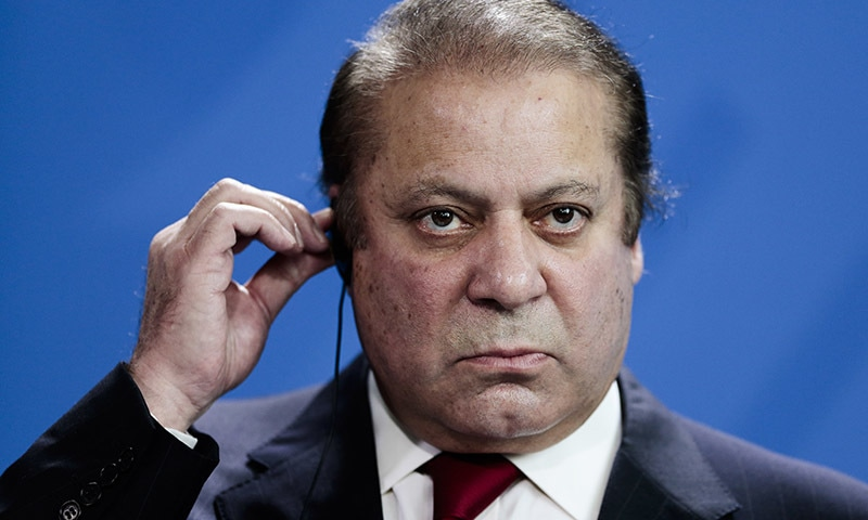 Pakistani Prime Minister Nawaz Sharif holds his ear phone as he attends a news conference. — AP/File