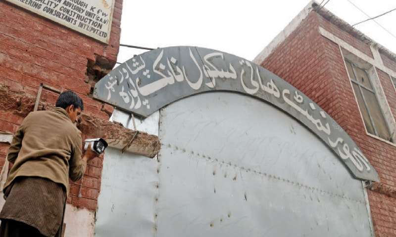 A worker installs a security camera at the entrance of a school in Peshawar on Sunday. —Photo by Shahbaz Butt