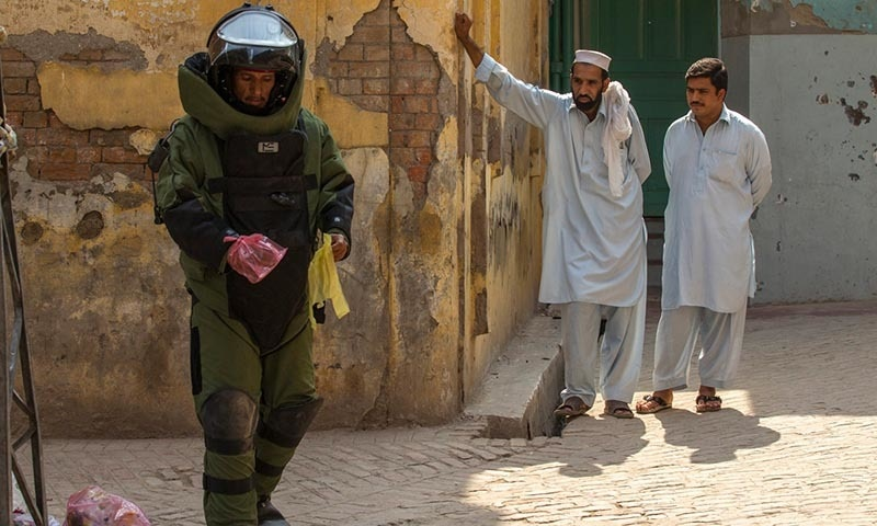 A technician from the bomb disposal unit uses plastic bags as gloves during a bomb search operation.   — Reuters/file
