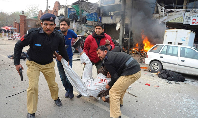 Police officers and volunteers rush an injured man to a hospital after a bombing in Lahore, Pakistan. — AP