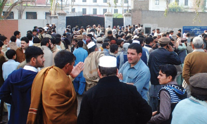 PEOPLE gather outside the girls college in Pabbi, Nowshera, on Tuesday. — White Star