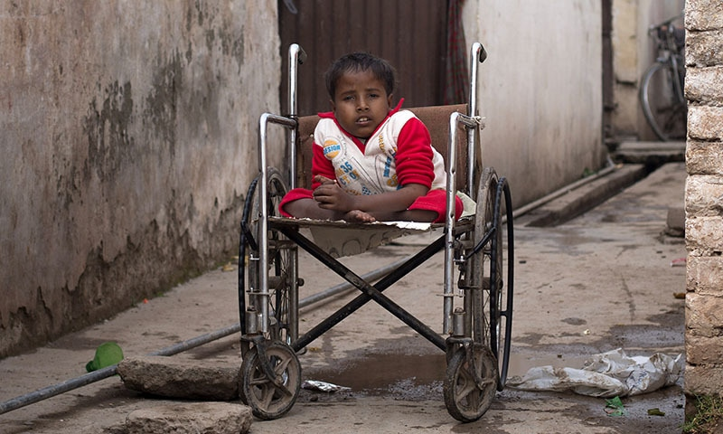 In this Tuesday, Feb. 17, 2015 photo, Sharjeel, who is paralysed due to polio, sits in his wheelchair outside his home in Islamabad, Pakistan. — AP
