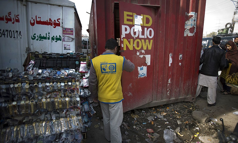 In this Tuesday, Feb. 10, 2015 photo, a Pakistani health worker enters his office situated in a shipping container at a bus terminal in Rawalpindi, Pakistan.— AP