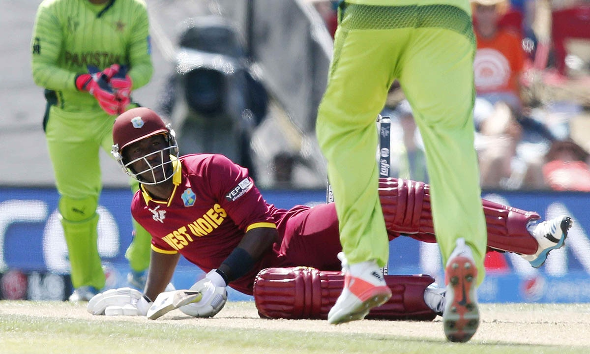 West Indies batsman Darren Sammy falls over as Sohail Khan (R) delivers a loose delivery. -REUTERS
