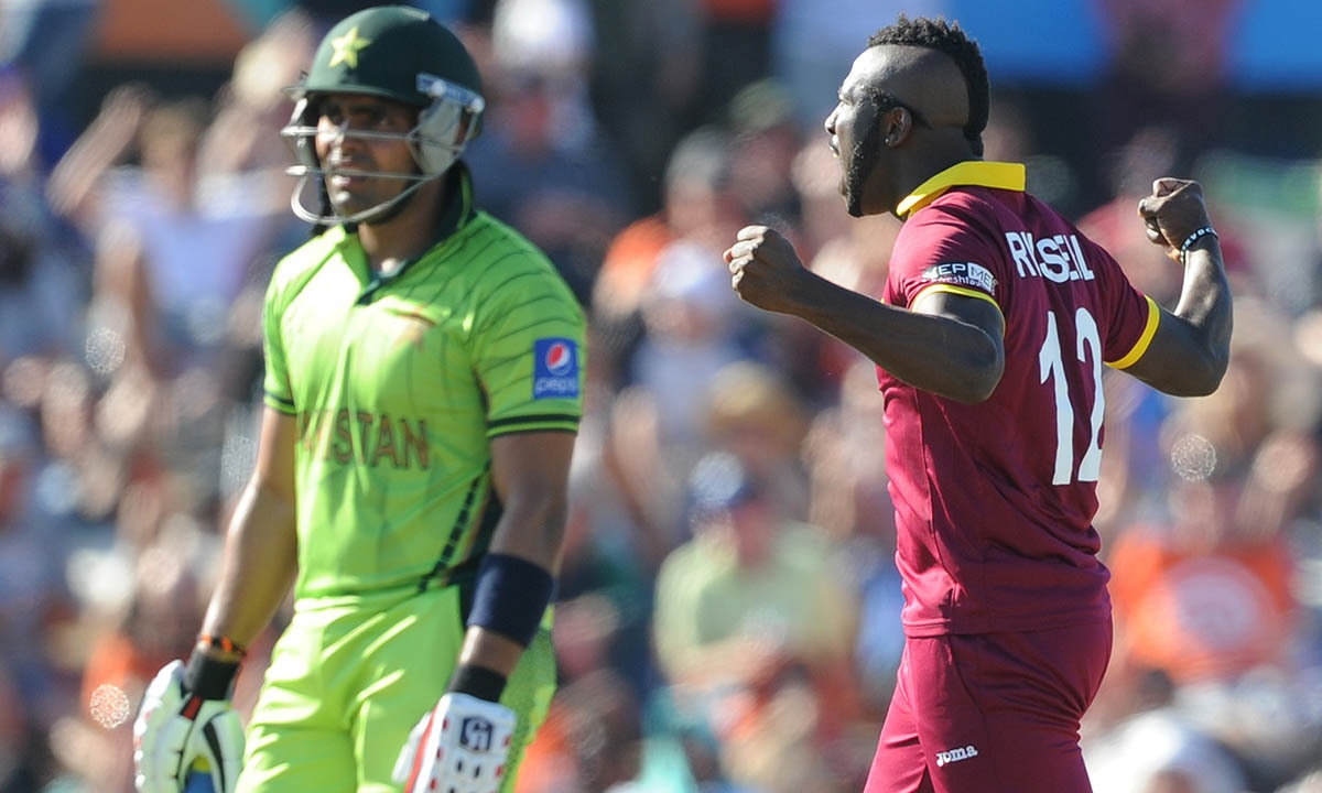 West Indies bowler Andre Russell, right, celebrates after dismissing Pakistan's Umar Akmal, left. -AP