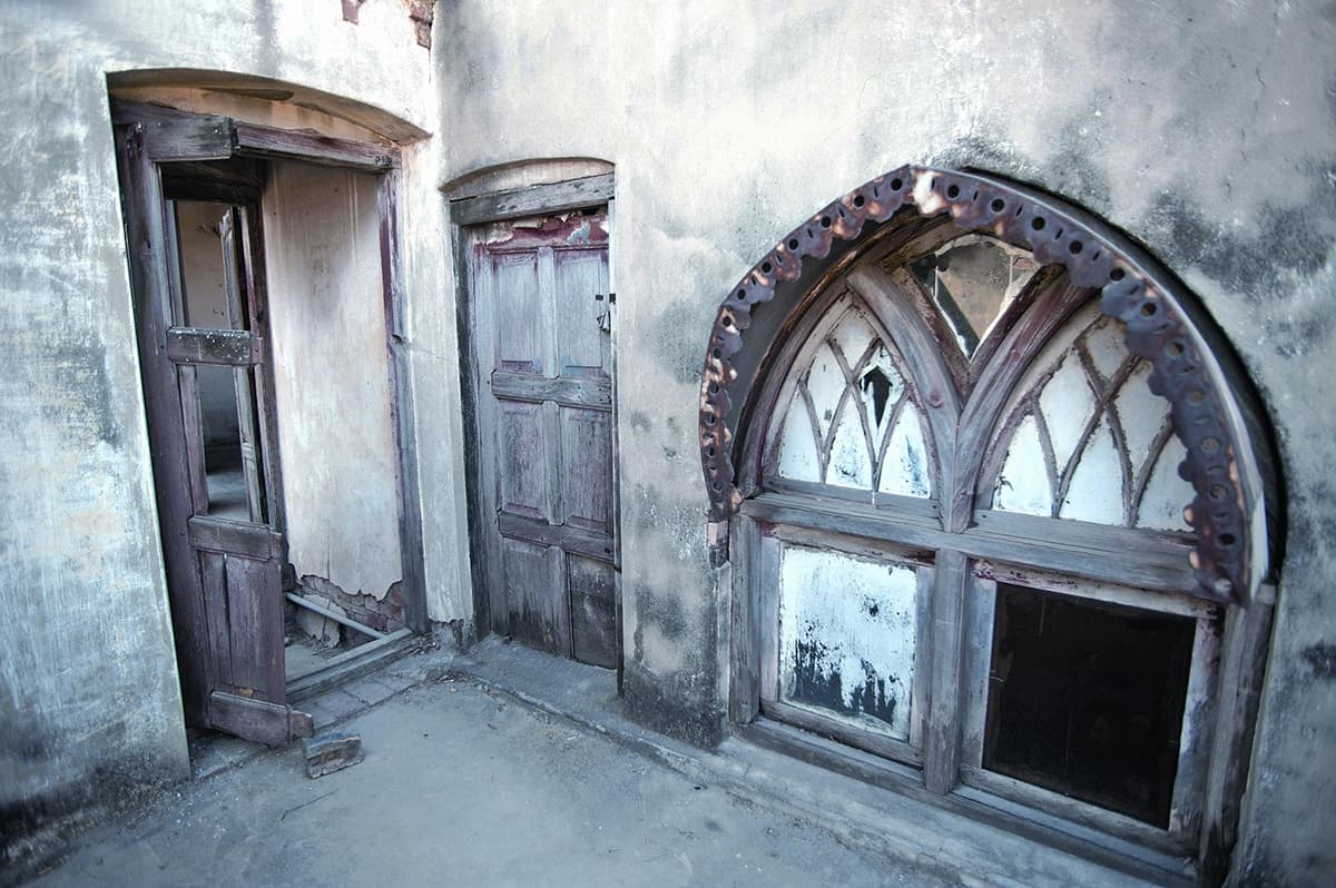 A stylised arched window with broken glass panes represents the dilapidated condition of Poonch House today. This was once part of the men's chamber.