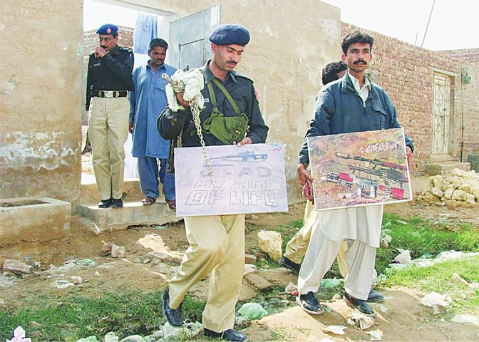 Kotri, 2007: Police personnel seize posters and literature from a madressa—Reuters file photo