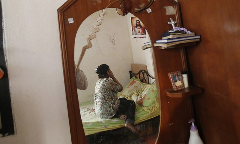 In this Monday, Jan. 12, 2015 photo, a Christian urban refugee from Pakistan who fled religious persecution sits on her bed in her room in the outskirts of Bangkok, Thailand.— AP