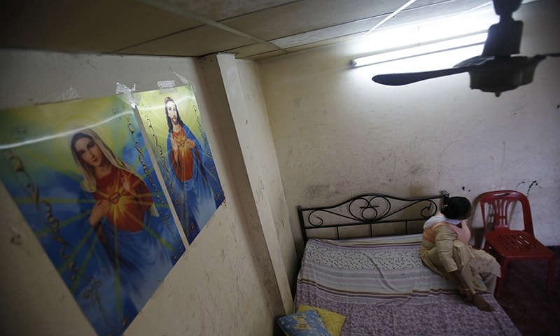 In this Jan 12, 2015, photo, an asylum-seeker sits on her bed in a one-room apartment on the outskirts of Bangkok, Thailand.— AP