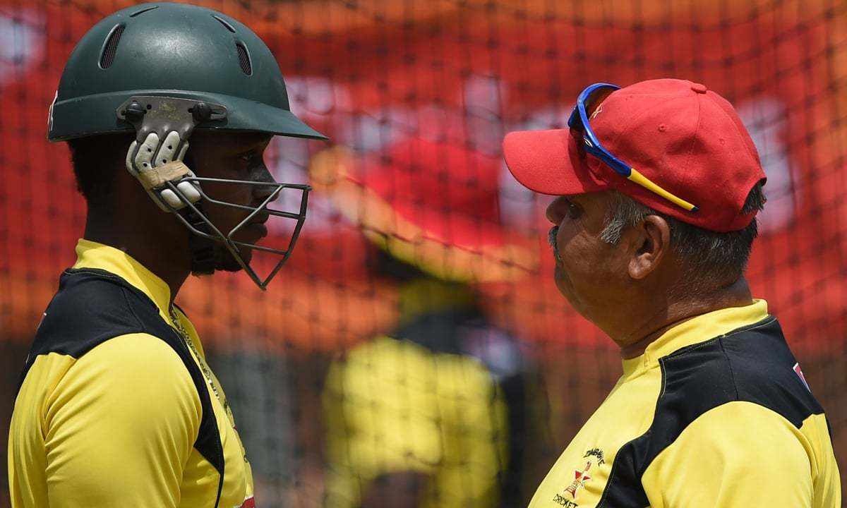 Zimbabwe cricketer Chamu Chibhabha (L) listens to coach Dave Whatmore during their training session. — AFP