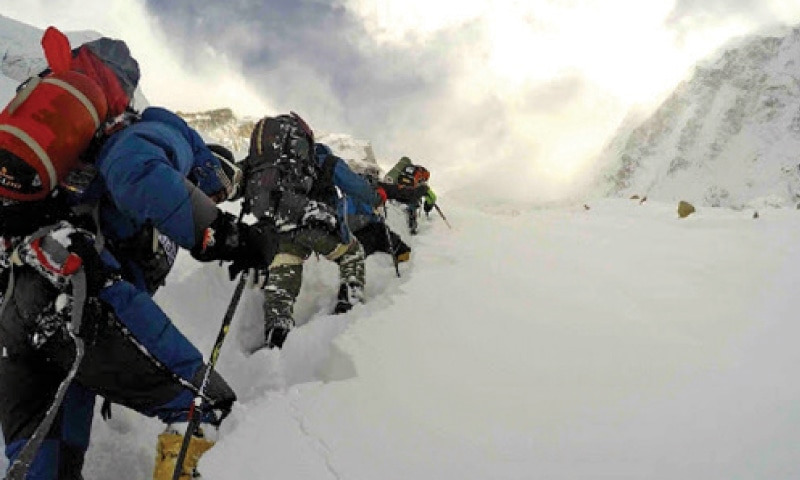After two weeks of heavy storm that dumped over five feet of snow, Pakistani, Iranian and Italian climbers step out of their tents to continue their attempt to climb Nanga Parbat. — Dawn
