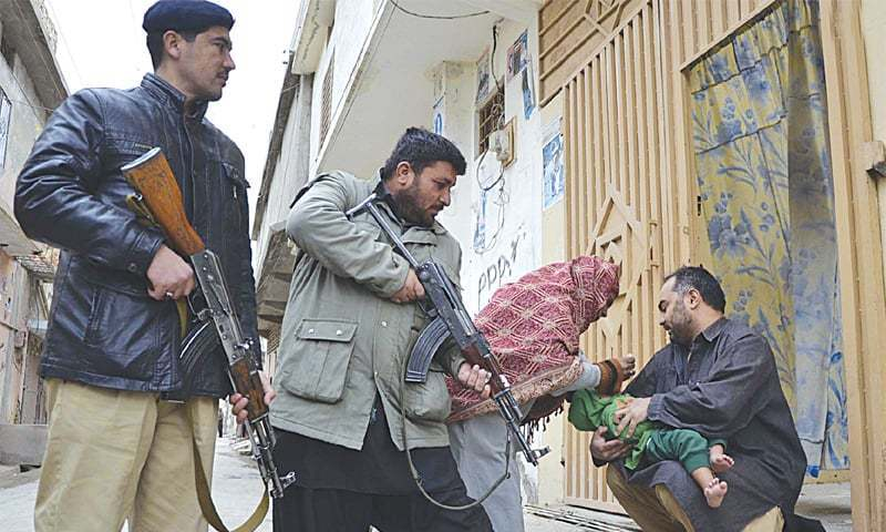 A health worker, guarded by security personnel, administers polio drops to a child in Quetta.—INP/file