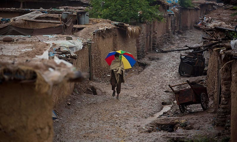 An Afghan refugee boy walks in an alley of a refugee camp in the rain.—AP/File