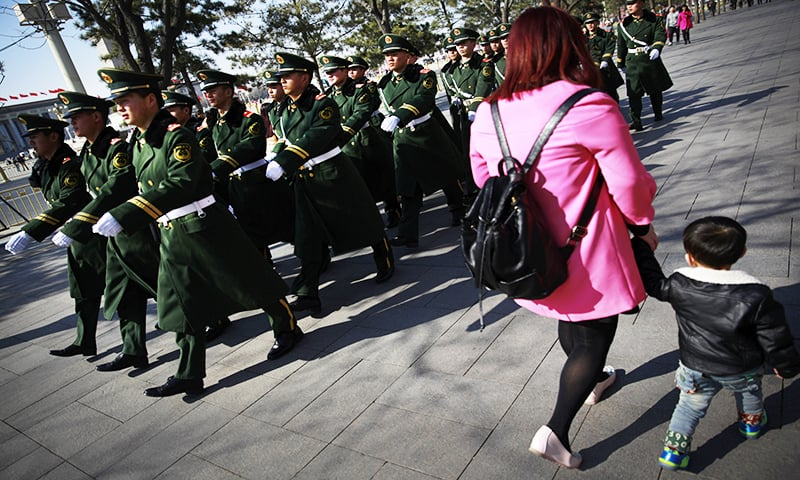 Chinese paramilitary policemen march past a woman and a child near Tiananmen Square in Beijing Wednesday, March 4, 2015 - AP Photo/Andy Wong