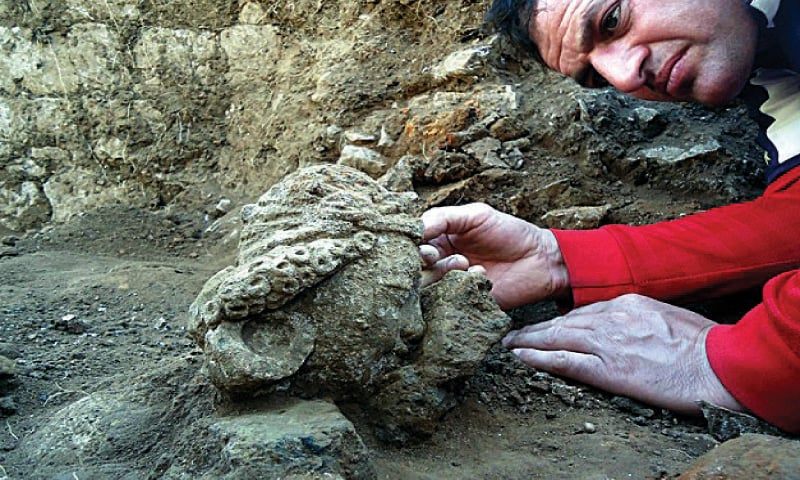 An archaeologist examines a head of Buddha discovered during excavation. — Dawn