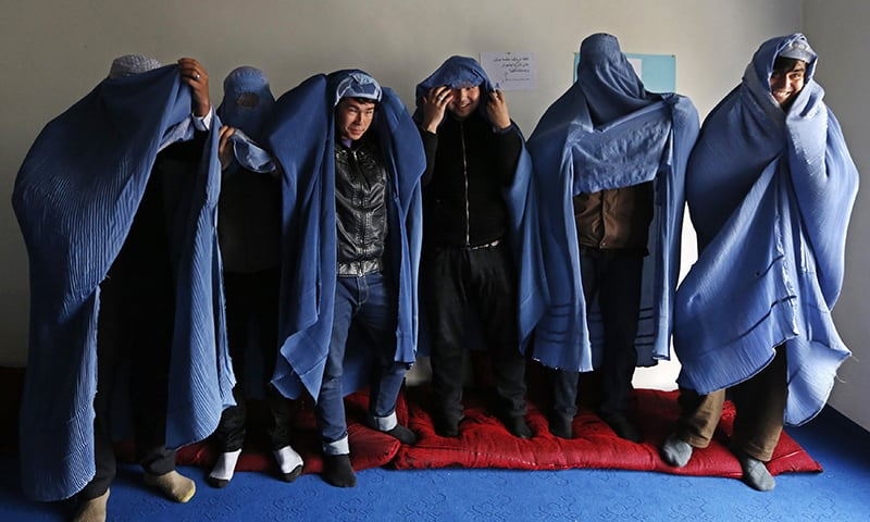 Male Afghan women's rights activist pose for media as they wear burqas to show their solidarity to Afghan women ahead of International Women's Day in Kabul, Afghanistan. — Reuters