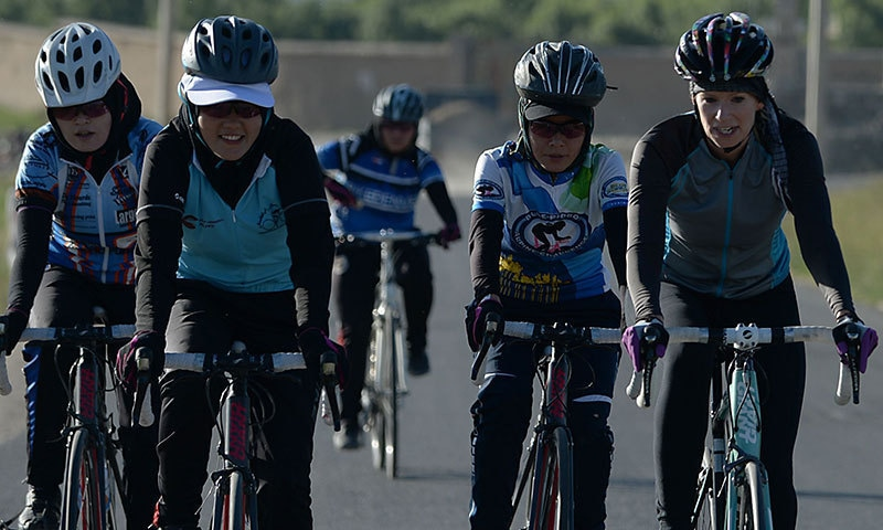 This photograph taken on June 9, 2014 shows members of the Afghan national women's cycling team riding their bikes in Paghman district of Kabul province. — AFP