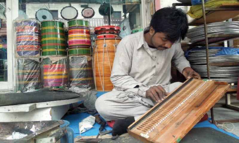 """Kamran Gill, 31, repairs a harmonium at his shop, """"Some of my family members sing, others play instruments. I am more comfortable repairing instruments at my workshop."""""""
