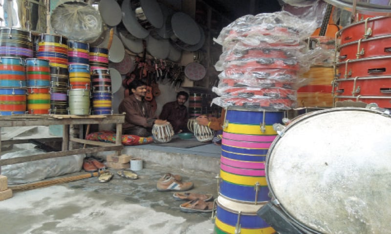 """Mujahid Hassan 'Labba', 42, sits at his shop along with his son Hamza, 13, and pupil Jahan, 39. """"I am proud that my father Tufail Hussain taught me this skill and now I am passing on this skill to the next generation."""""""