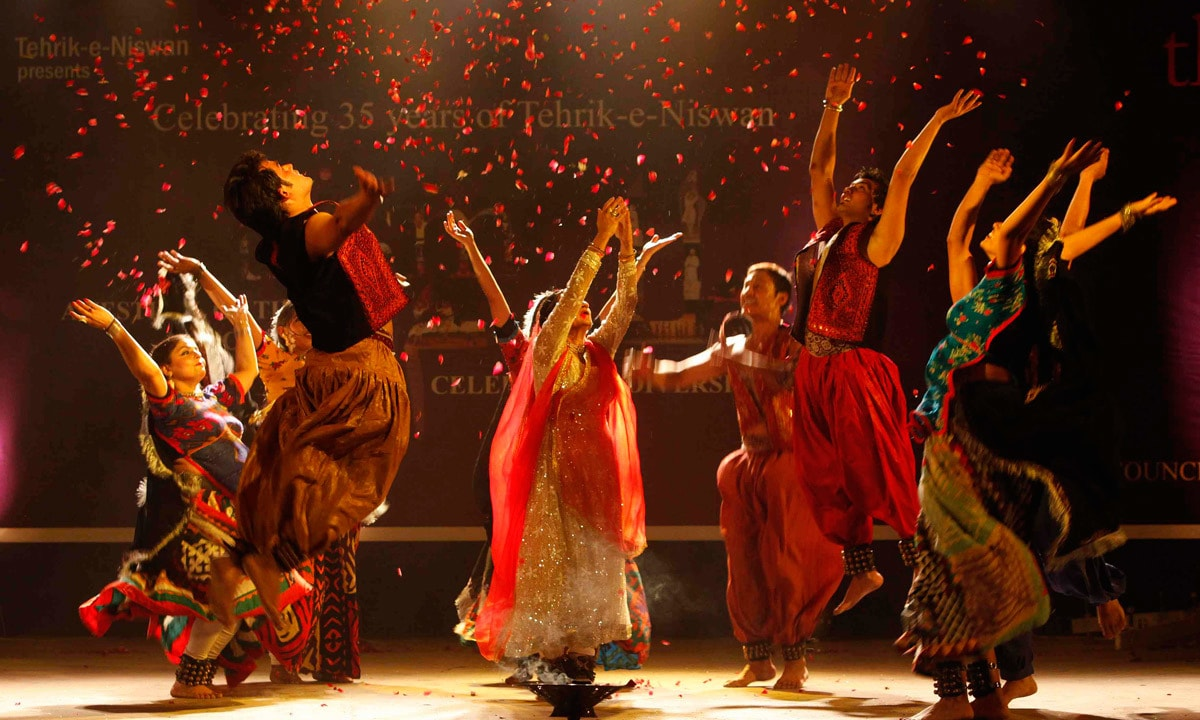 Sheema Kirmani  and her troupe throw rose petals while performing during the festival of theatre. – Reuters