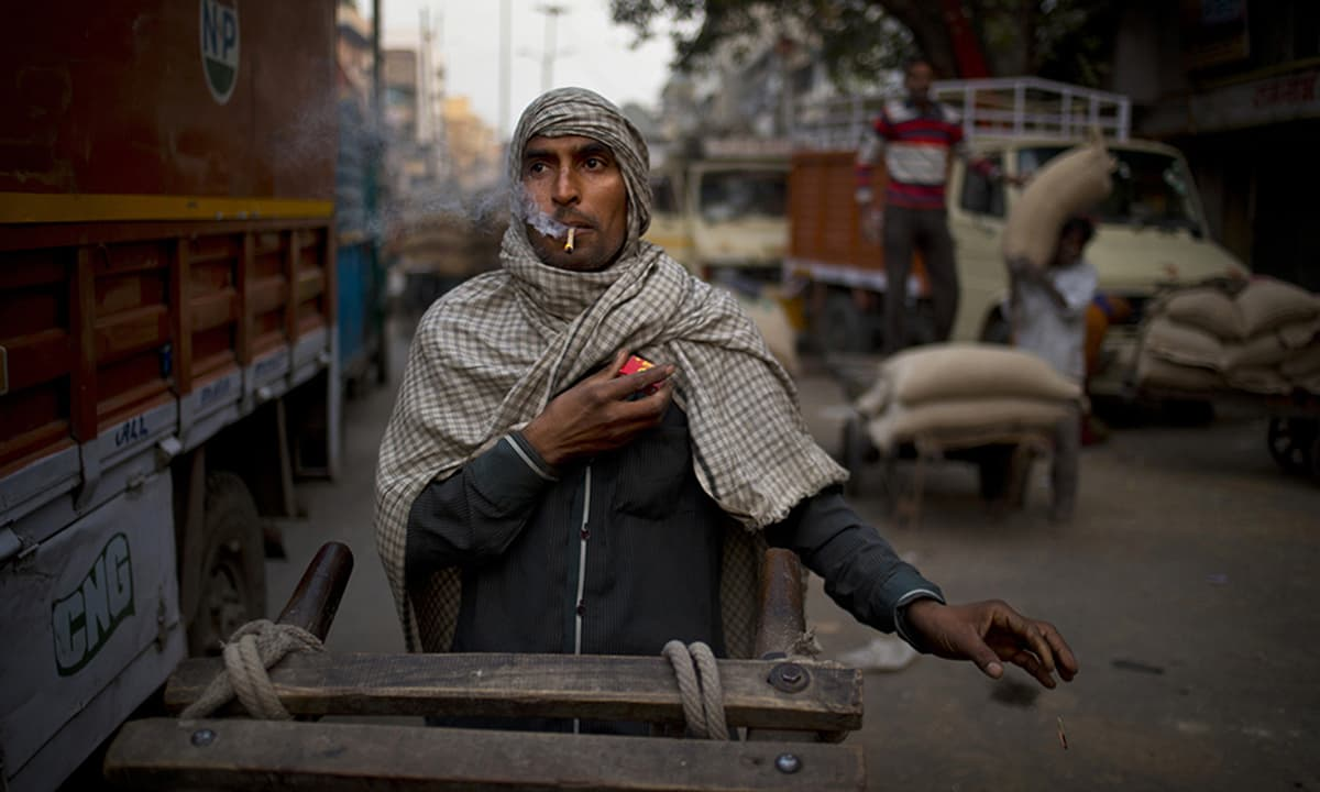 A cart puller smokes a beedi, tobacco rolled in an indigenously available leaf, as he waits for traffic to clear in New Delhi, India. Cart pullers who own their carts make $4-10 a day.— AP