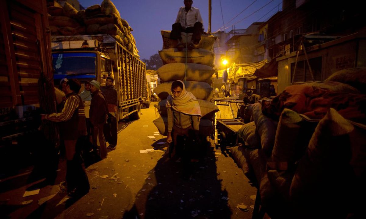 A cart puller sits on top of a load of goods and makes a call from his mobile phone to family members back home at the khari baoli spice market in New Delhi, India. Many Cart pullers work until they've saved enough to head home for a few months to see their families. And when the money runs out, they come back again to Khari Baoli.— AP